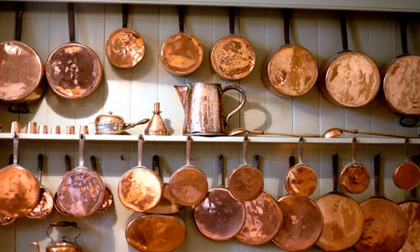 Copper pots and pans hanging in a kitchen
